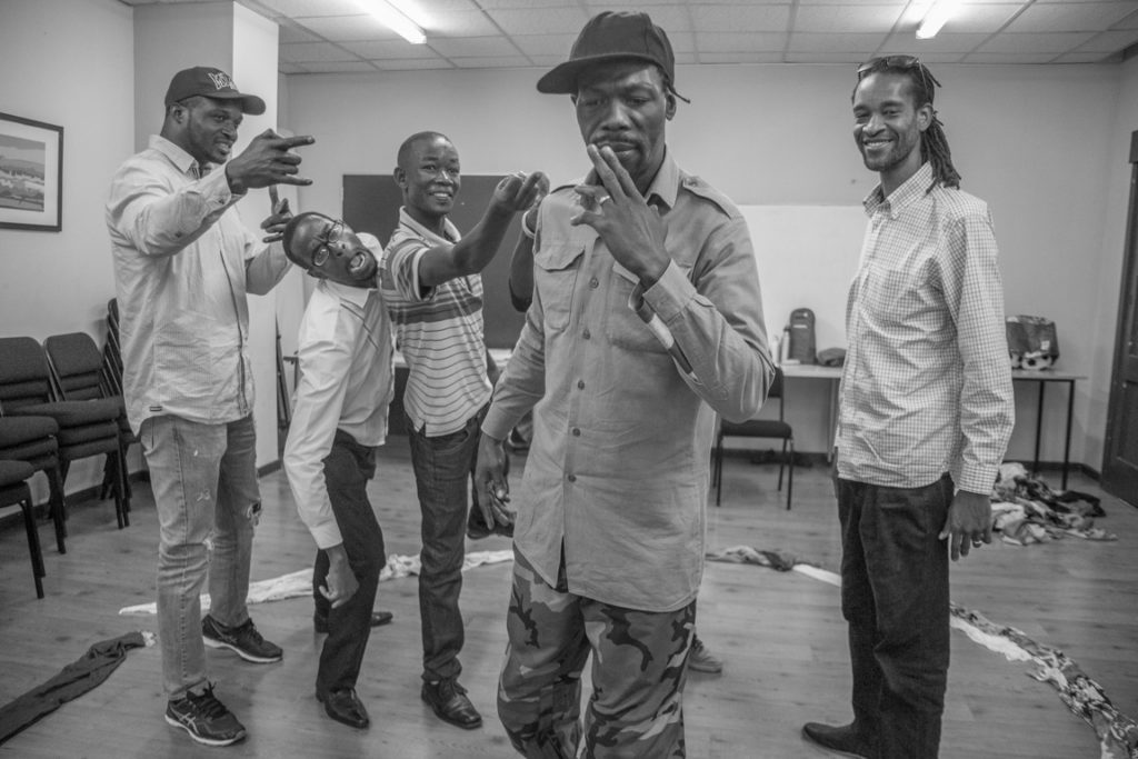 The men's group re-enact a group member's memories of being ostracised by local people after arriving in Cape Town.